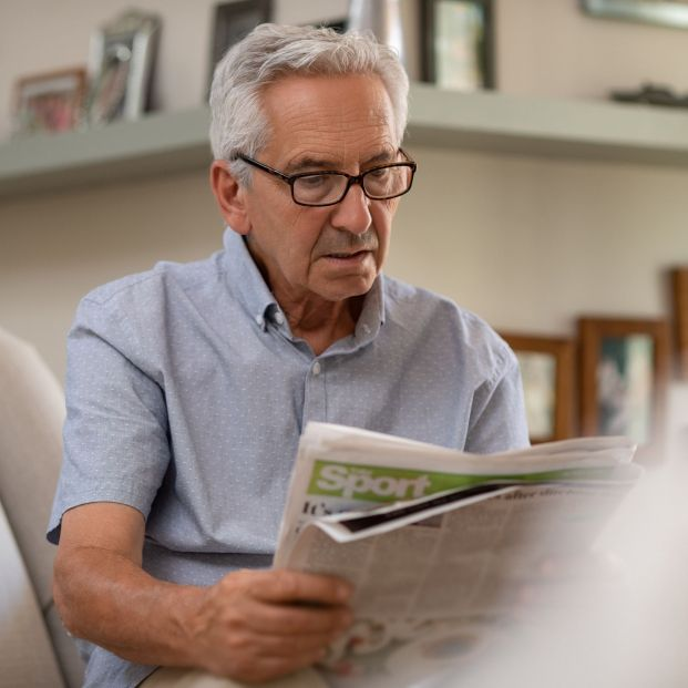 Practical advice to take care of eye health.  Adult person with glasses reading newspaper at the correct distance (bigstock)